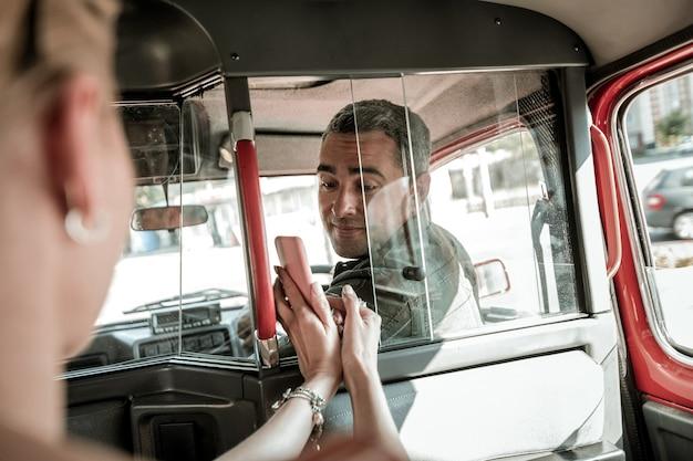 운전할 곳. 웃는 자동차 운전사에게 지도와 함께 그녀의 스마트폰을 보여주는 뒷좌석에 앉아 있는 여자.