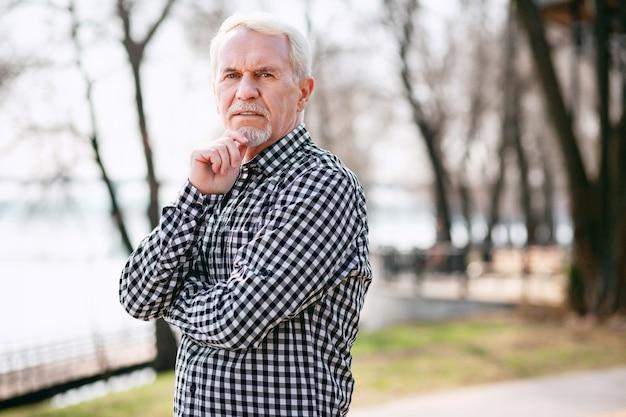 Куда идти. вдумчивый старший мужчина позирует в парке и трогательно лицо