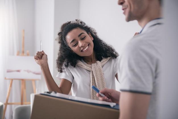 서명 할 곳. 배달 남자에게 서명을 요구하는 동안 펜을 들고 쾌활한 행복한 여자 프리미엄 사진