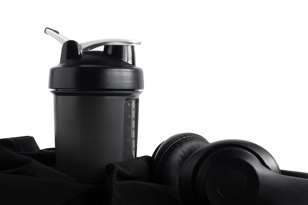 Whey protein shaker bottle with headphone on black sportswear isolated on white