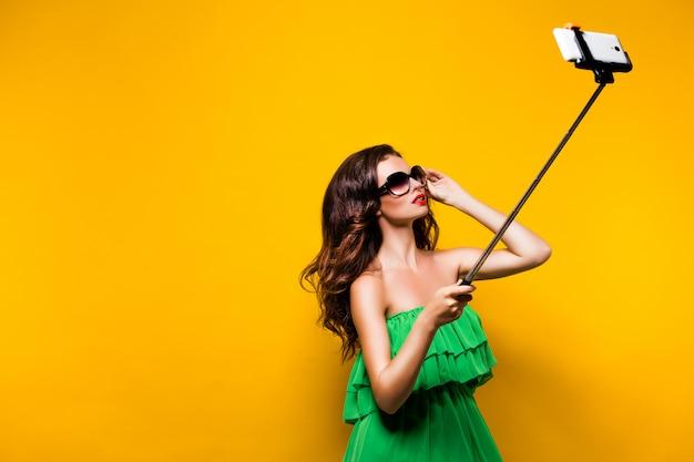 Портрет молодой модели в зеленом платье и солнцезащитные очки, позирует whi