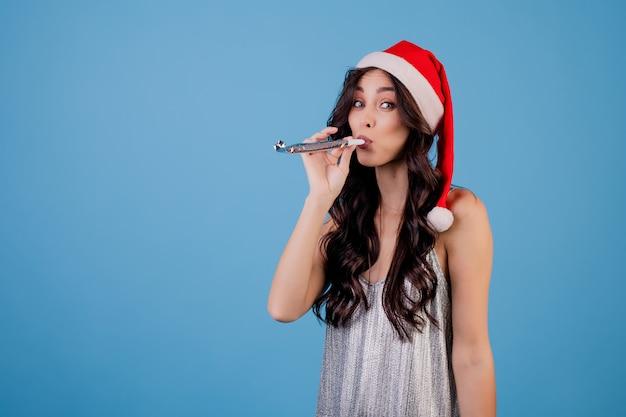 青で分離されたクリスマスwhiを吹くクリスマス帽子をかぶっている女性