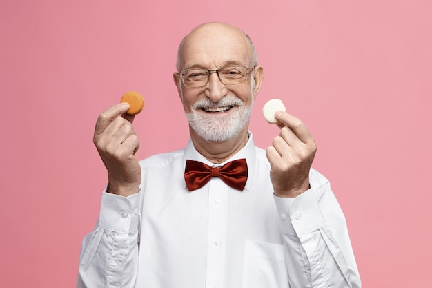 Which one do you like? isolated image of cheerful energetic senior retired male wearing glasses and bow tie, smiling broadly, holding colorful macarons in each hand, offering you to have some