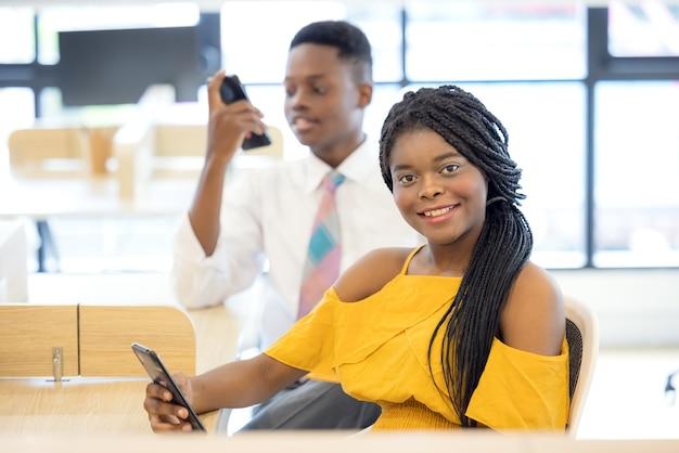 Сидя на красивой кушетке в читальном зале, улыбающаяся темнокожая женщина со смартфоном ищет информацию для своего доклада. образование и технологии Premium Фотографии