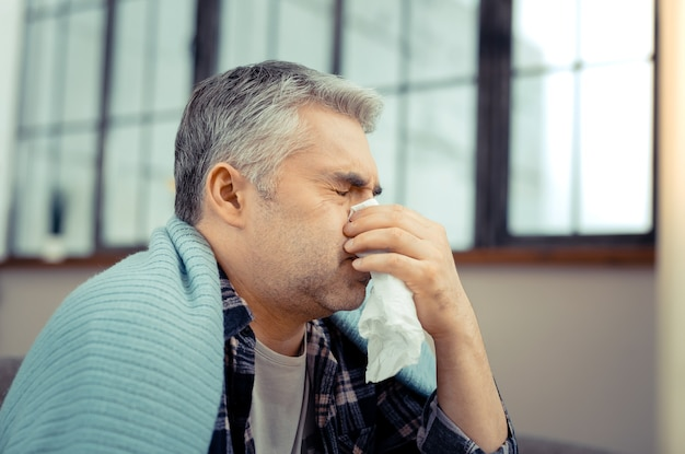 While sneezing. cheerless sick man using a paper tissue while sneezing in it