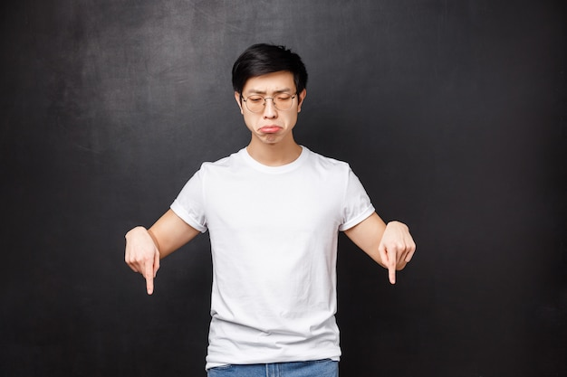 Whining and sobbing miserable upset asian guy feel gloomy, grimacing uneasy and distressed, looking pointing down, losing didnt won prize, regret of missed opportunity,