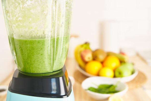 Взбивая смесь ягод, фруктов и овощей в блендере, готовим веганский зеленый смузи