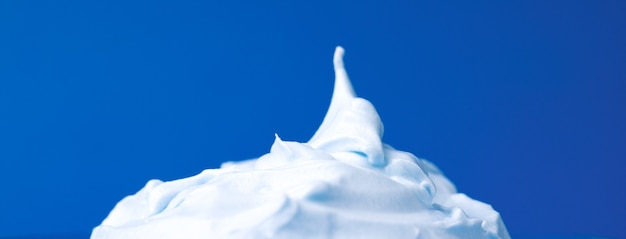Whipped cream over blue background, panoramic image