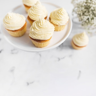 Whipped cream cupcakes on cake stand