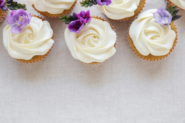 Whipped cream frosting vanilla cupcakes with purple edible flowers