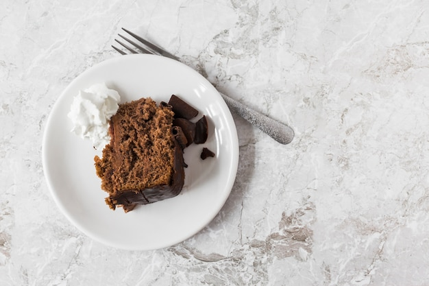 Whipped cream and slice of cake on plate with fork over the marble counter