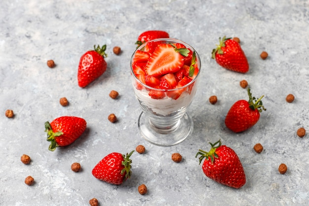 Whipped cream and strawberry trifle with honey and cereals.