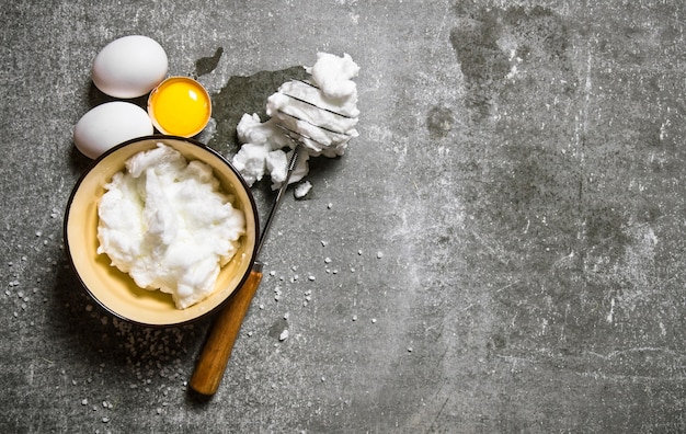 Whipped eggs in a bowl with a whisk. on a stone table. free space for text . top view