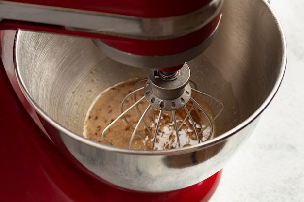 Whipping eggs with sugar in the bowl of the mixer