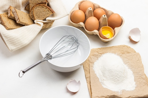 Whisk in bowl. flour on paper. eggs in cardboard container. toast on white napkin. top view