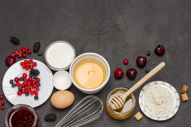 泡立て器、壊れた卵のボウル。小麦粉、ベリーミルク、バター、ハニージャム。朝食を調理するための材料。コピースペース。フラットレイ