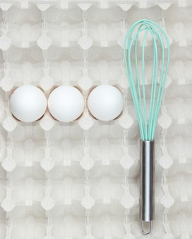 Whisk and eggs in tray. top view, closeup