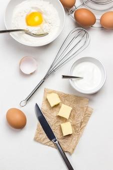 테이블에 털다. 종이에 칼과 버터. 그릇에 깨진 계란과 밀가루. 플랫 레이