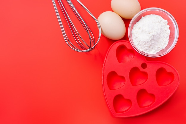 Whisk, red silicone mold and ingredients for a dessert on a festive table on valentine's day.