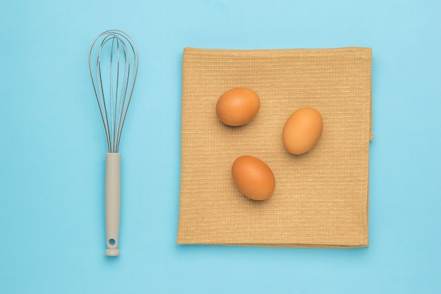 A whisk for whipping and three eggs on a piece of cloth on a blue surface. natural products and kitchen equipment.