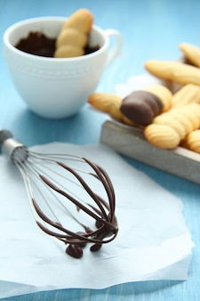 Whisk with melted chocolate and homemade shortbread cookies on blue wooden background