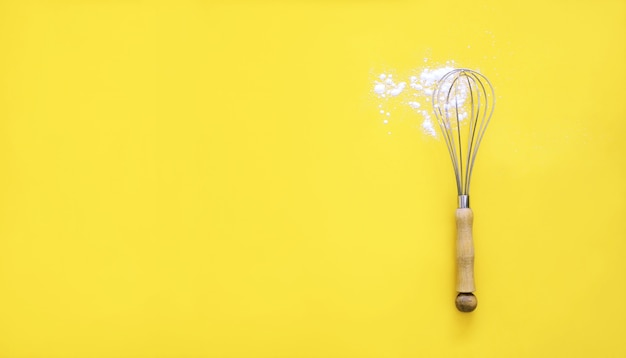 Whisk with wooden handle and white wheat flour on yellow background.