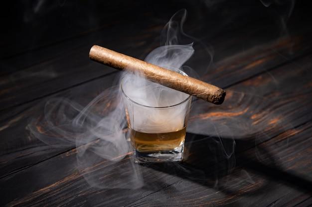 Виски и сигара на деревянных фоне крупным планом