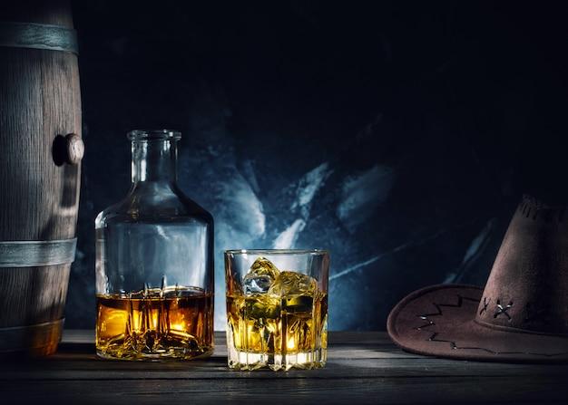 Виски, шляпа и бочка на темном
