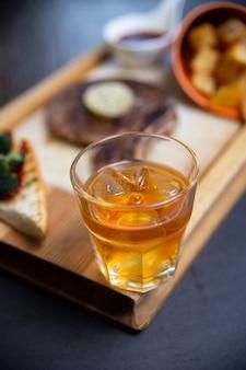 木の板にウイスキーとステーキ。