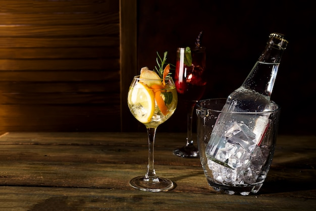 ウィスキーベースのダークウッドのbackgorundにグラスアイスバケツとカクテル