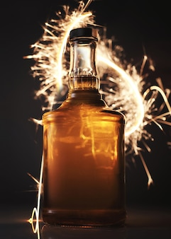 Whiskey bottle on festive fire background