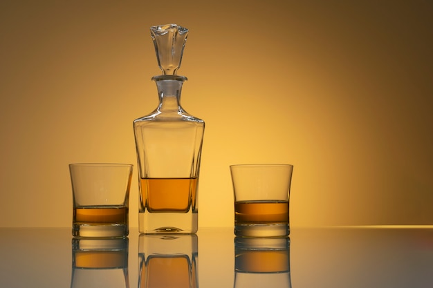 Whiskey bottle with two glasses with reflection on glass table and light yellow background
