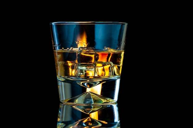 Whiskey or bourbon in a transparent glass with ice cubes on a black with fire