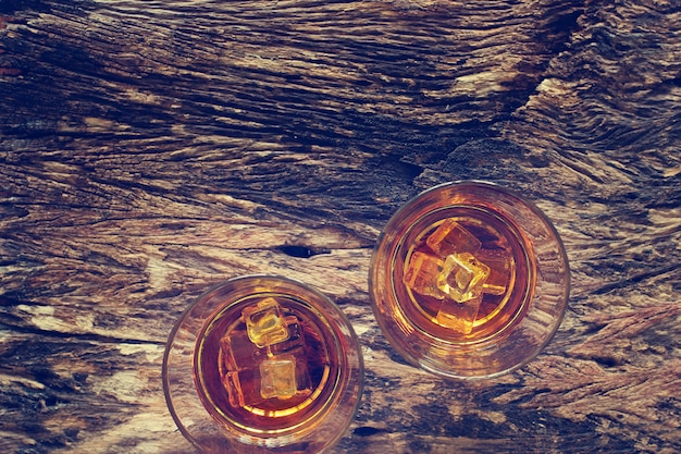 Whiskey bourbon with ice on wooden texture background.