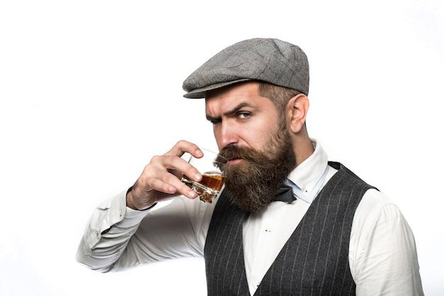 Виски, бренди, коньячный напиток. брутальный бородатый мужчина с бокалом виски, бренди, коньяка.