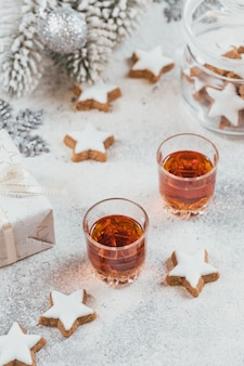 Whiskey, brandy or liquor, cookies and chrastmas decorations on white background