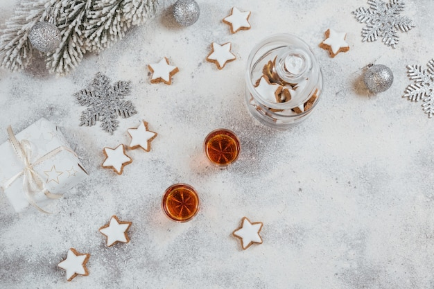 Whiskey, brandy or liquor, cookies and christmas decorations on white