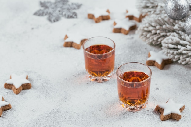Whiskey, brandy or liquor, cookies and winter holiday decorations on white