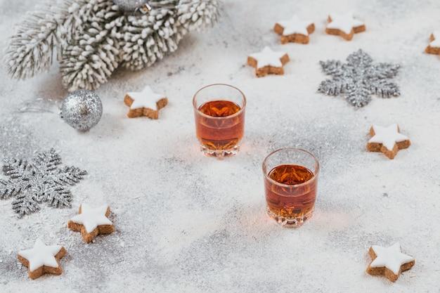 Виски, бренди или ликер, печенье и рождественские украшения на белом
