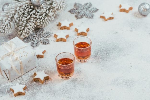 위스키, 브랜디 또는 주류, 쿠키 및 흰색 배경에 겨울 휴가 장식