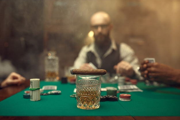 Whiskey and cigar on gaming table with green cloth, bearded poker player in casino
