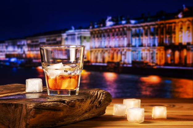 Whiskey cocktail with ice on wooden table