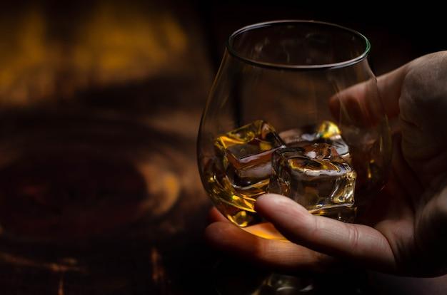 木の上の手で氷とウイスキー/コニャックグラス