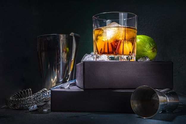 Whiskey or cognac in glass, with lime, ice cubes ans barmen utensils, dark background with on stand pedestal copy space