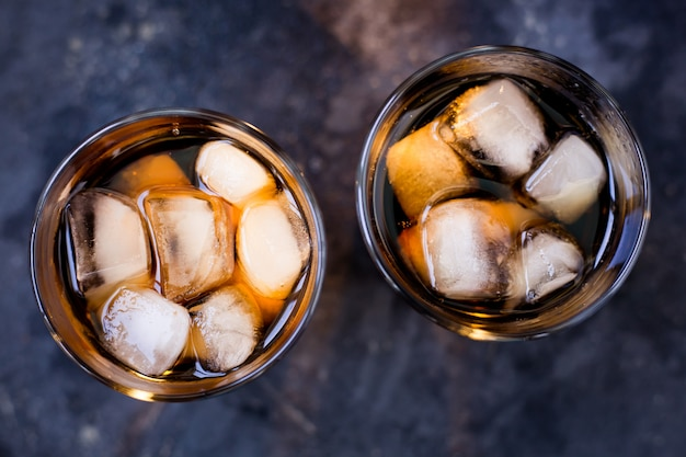 Whiskey and cola and ice in glasses on a dark gray background