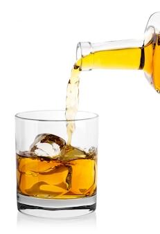 Виски из бутылки наливают в стакан с кубиками льда