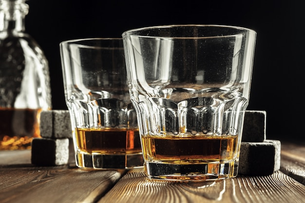 Whiskey glass and bottle on the old wooden table