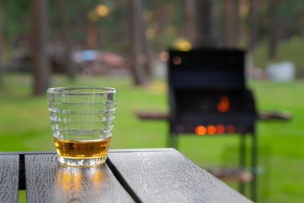 Стакан виски на деревянном столе рядом с горящим грилем на открытом воздухе на заднем дворе.