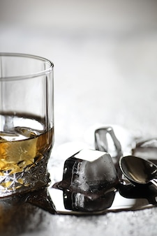 Whiskey in a glass and pieces of ice on a wooden table