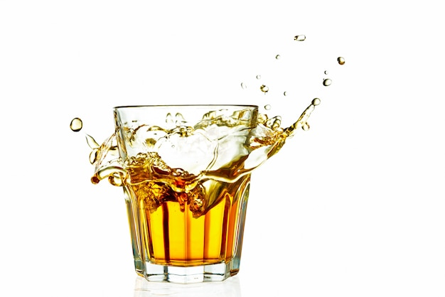 Whiskey in a glass splash isolated on white background with reflection
